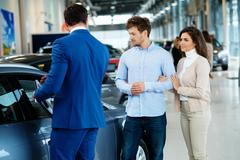 Salesman talking to a young couple at the dealership showroom Stock Photos