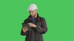 Mid Shot of a Handsome Worker Wearing White Hard Hat Using Tablet Computer  Stock Footage