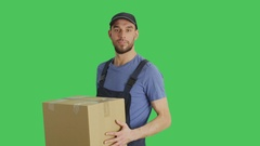 Mid Shot of a Handsome Loader Handing in Cardboard Box. Shot with Green Screen  Stock Footage