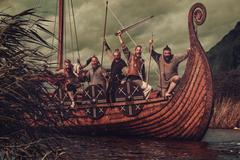 Group of vikings are floating on the sea on Drakkar with mountains on the Stock Photos