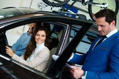 Beautiful young woman buys a car in the dealership saloon Stock Photos