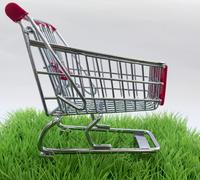 Original background on purchases with green grass and shopping basket Kuvituskuvat