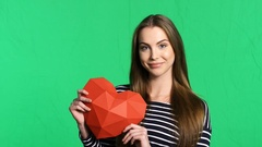 Smiling woman holding red polygonal paper heart shape Stock Footage