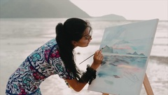 Young girl draws a sunrise, on the beach at low tide. Stock Footage