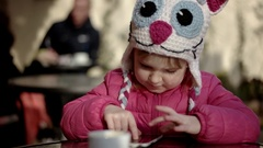 Pretty Little Girl Using App on Smartphone Sits in the Street Terrace Stock Footage