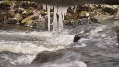 Icicles hang above cold water of mountain river. Icicles glitter above stream Stock Footage
