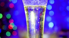 Bubbles sparkling wine in glass. In the background, bokeh lights and garlands Stock Footage