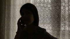 Girl talking on a cell phone near a window Stock Footage