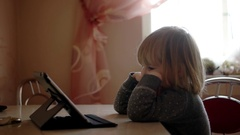 Pretty Little Girl Watches Cartoon Ontablet Computer Sits on the Kitchen Table Stock Footage