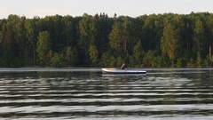 Alone man riding on a rowing boat on the lake dusk time. Sunset sunrise on the Stock Footage