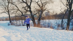 Funny girl happily running in the snow, is happy onset of winter Stock Footage