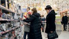 People choose gifts in Auchan hypermarket Stock Footage
