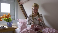 Young Woman Wraps Tea Bag Around Spoon, Drops A Sugar Cube In, Chats, Smiles Stock Footage