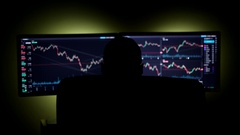 Stockbroker is Working on the Financial Market in a Dark Monitoring Room With Stock Footage