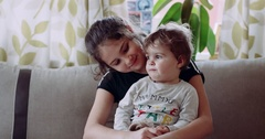 A child sitting in his sister's arms and she looks at him and smiled. 4k Stock Footage