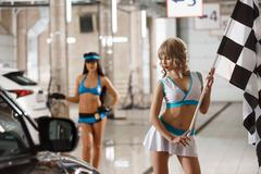 Two sexy girls in formula 1 style pose at carwash Kuvituskuvat