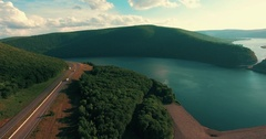 Clip shows a birds eye view of trucks passing on a highway next to a lake and mo Stock Footage