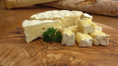 Soft brie cheese cubes on rustic board Stock Footage