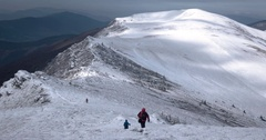 A Group of Hikers With Backpacks Full of Gear Hike Along a Snow Covered Stock Footage