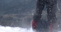 A Girl With a Backpack Travels Snowy Mountains While Wind Blowing Over the Snow Stock Footage