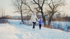 A woman with a child laughing in a winter park. Girl runs about mom and enjoys a Stock Footage