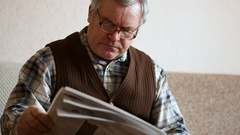 Old man reading the newspaper at home Arkistovideo