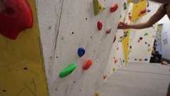 Detail of a man's shoes as he climbs in an indoor climbing gym. Stock Footage