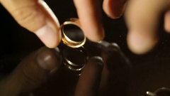 Golden wedding rings whirl on glass table Stock Footage