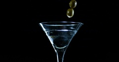 Martini being garnished with green olive in slow motion Stock Footage