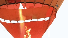 Man lights up fire under red air balloon Stock Footage
