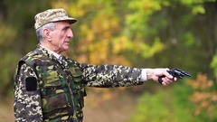 Senior man in military uniform shoots a revolver Stock Footage