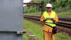 Railwayman makes notes in his tablet computer Stock Footage