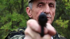 Man with black gun looks at the camera Stock Footage