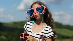 Girl with smartphone stands on meadow, listens to music, dances and sings a song Stock Footage