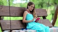 Beautiful girl sits on the swing bench in garden and speaks via smartphone HD Footage