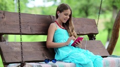 Beautiful girl sits on the swing bench in garden and speaks via smartphone Stock Footage