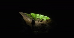 Spelunker Cautiously Enters a Limestone Cave - 4K Stock Footage