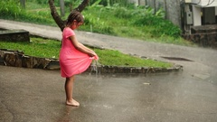 5 year old girl having fun during a heavy tropical rain Stock Footage