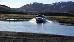 Fixed shot of a car crossing a ford near Landmannalaugar, in Iceland Stock Footage