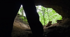 Caver Exits Dark Cavern into Lush Forest Stock Footage