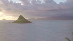 Drone aerial of dawn at Kualoa and Mokolii Island with Palm tree silhouettes Stock Footage
