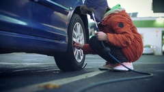 Technical Shot of a Mechanic Boy Pumping up Tyres Stock Footage