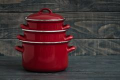 New And Clean Covered Red Saucepans on Blue Wooden Background. Stock Photos