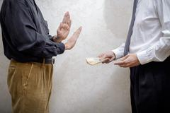 Man Offering  a Hryvnia bribe to a Man Refusing it Stock Photos