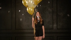 Young Girl with Long Hair in Short Dress Holds Gold and White Balloons, Silver Stock Footage