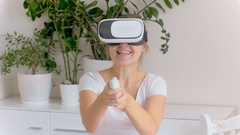 Cheerful young woman wearing VR headset playing in 3d shooter game Stock Footage
