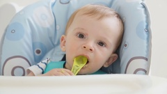 Cute baby boy eating soup with spoon by himself and getting messy Stock Footage