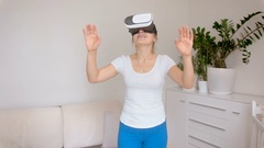 Cheerful and amazed woman wearing virtual reality headset walking in room Stock Footage