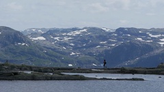 Fixed shot of hiker in Norway, with snowy mountains Stock Footage
