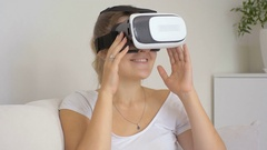 Young woman in virtual reality glasses watching 3d movie on sofa Stock Footage